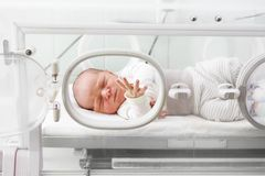 Newborn baby in an incubator. A newborn baby in an incubator in a hospital ward stock images