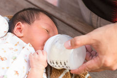 Newborn baby infant eating milk from bottle. Stock Image