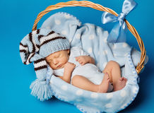 Newborn Baby Inside Basket, New Born Kid Dream in Woolen Hat. Little Child Boy Sleeping over Blue Background Stock Image