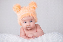 Newborn baby in a knitted cap with ears. Stock Photo