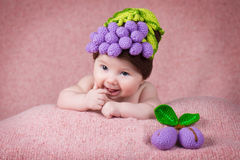 Newborn baby a knitted cap in the form of grapes. stock photos