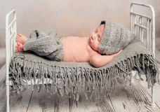 Newborn baby in knitted hat and pants sleeping on old cot Stock Photography