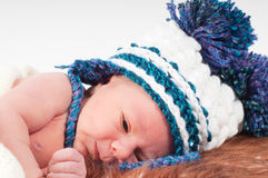 Newborn baby in knitted hat with pom-pons Stock Photography