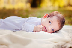 Newborn baby laying on the grass Stock Photo