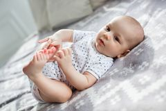 A newborn baby lies on the bed in the bedroom Royalty Free Stock Images