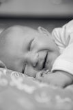 Newborn baby lies and smiles. In his sleep Royalty Free Stock Photography