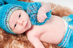 Newborn baby in long blue knitted hat Stock Photography