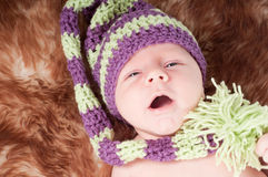 Newborn baby in long knited hat Stock Images