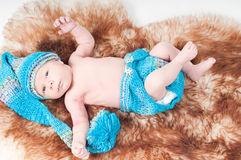 Newborn baby in long knitted hat Royalty Free Stock Photo
