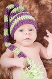 Newborn baby in long striped hat Stock Photos