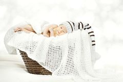 Newborn Baby Lying in Basket, New Born Child Woolen Knitted Hat stock photo