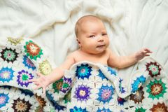 Newborn baby lying on bed, covered by a crocheted blanket. Top view. stock photo