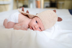Newborn baby lying on bed and dressed in funny baby clothes in b Royalty Free Stock Images