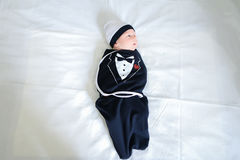 Newborn baby lying on bed and dressed in funny baby clothes in b Royalty Free Stock Photo
