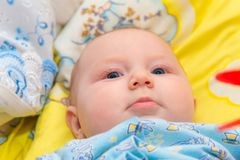 Newborn baby is lying in the baby bed on a yellow background and smiling, close-up stock images