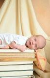 Newborn baby lying on  books Stock Images