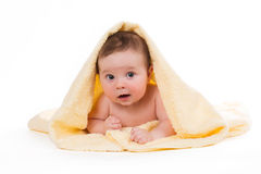 Newborn baby lying down and smiling in a yellow towel Royalty Free Stock Photos