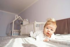 A newborn baby is lying on his stomach in the nursery on the bed. royalty free stock photography
