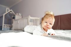 A newborn baby is lying on his stomach in the nursery on the bed royalty free stock image