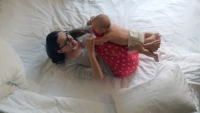 Newborn baby lying on mother legs. Baby workout. Child nursing at home stock video