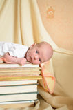 Newborn baby lying on pile of books Stock Image