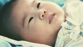 Newborn baby lying and relaxing on the bed. Healthy children concept. Cinematic style colors. Close up face of a two-month adorable asian baby relaxing and stock footage