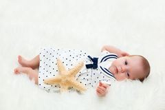 Newborn baby lying on white fur. Maritime composition with starfish and sailor dress. Royalty Free Stock Image