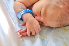 A newborn baby with a maternity hospital bracelet on his arm is sleeping in a crib. A newly born child in a clinic bed behind a