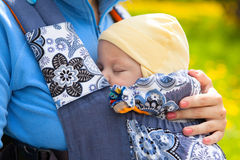 Newborn baby and mother outdoors walking with sling. Stock Photos