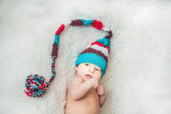 Newborn baby in New Year`s gnome Cap lays On a white blanket.  stock photography