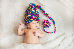 Newborn baby in New Year`s gnome Cap lays On a white blanket.  royalty free stock photography