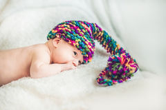 Newborn baby in New Year`s gnome Cap lays On a white blanket.  stock photos