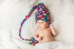 Newborn baby in New Year`s gnome Cap lays On a white blanket.  stock photo
