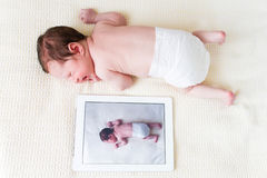 Newborn baby next to her photo on a tablet pc Stock Photography