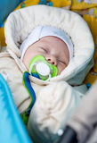 Newborn baby with a pacifier lying in a stroller Royalty Free Stock Image