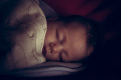 Newborn baby peaceful sleeping in dark room with low natural light covered with comfortable blanket symbolize peace Stock Image