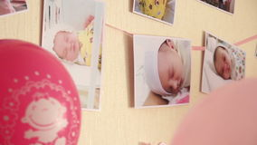 Newborn baby photos hanging on the wall with balls. stock video footage