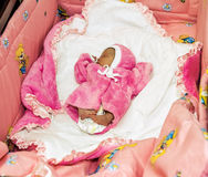 A newborn baby in pink clothes sleeps in a crib Stock Photography