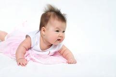 Newborn baby in pink dress looking away Stock Photo