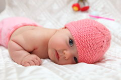 Newborn baby in pink hat. Lying on a bed Royalty Free Stock Image