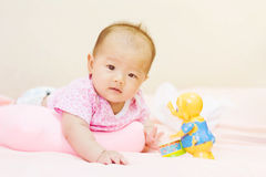 Newborn baby playing on colorful toy Royalty Free Stock Photos