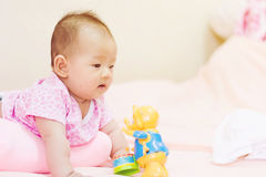 Newborn baby playing on colorful toy Royalty Free Stock Images