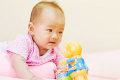 Newborn baby playing on colorful toy Stock Photography