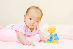 Newborn baby playing on colorful toy Stock Photos