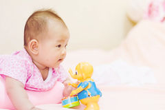 Newborn baby playing on colorful toy Royalty Free Stock Image