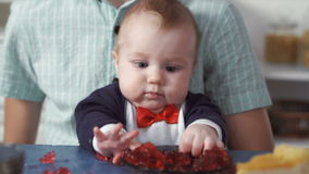 Newborn baby plays with food stock video footage
