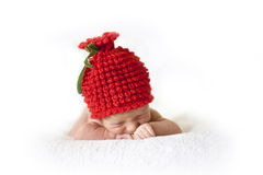 Newborn baby in a red berry cap Stock Images