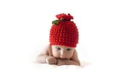 Newborn baby in a red berry cap Royalty Free Stock Photography