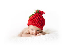 Newborn baby in a red berry cap. Newborn baby in a red hat on a white background Royalty Free Stock Photo