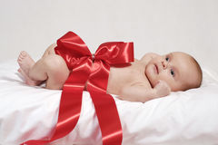 Newborn baby in the red bow Stock Images